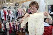 Amy Laughlin, owner of Second Chance Children's and Maternity Store, 847 Mass., sorts children's clothes. Laughlin, pictured on Friday, is a survivor of breast and liver cancers.