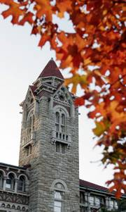 The Natural History Museum tower on Kansas University's campus shares the sky with the turning leaves of a maple tree found across the street.
