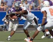 Kansas State running back Leon Patton (14) is tackled by Oklahoma State's Victor DeGrate. Patton, a freshman who started his first game Saturday, ran for 151 yards and returned a kickoff for a touchdown in the Wildcats' 31-27 victory against the Cowboys in Manhattan.