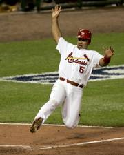 St. Louis' Albert Pujols slides into home to score on Juan Encarnacion's triple. St. Louis elimated the Padres in Game 4, 6-2, Sunday in St. Louis.