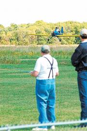 "Topeka&squot;s Ken Bina, left, pilots his big remote-control aircraft with Snoopy at the helm during the ""Jayhawk Big Bird Fly-in."" The event was held last month at the Clinton International Model Airport by the Clinton Lake dam."