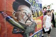 South Korean tourists look at a defaced cartoon of North Korean leader Kim Jong Il put up Sunday during an anti-North Korea rally at the Imjingak Pavilion, near the demilitarized zone of Panmunjom, South Korea. North Korea today said it had conducted an underground nuclear test, despite strong opposition from its neighbors, including China, its closest ally.
