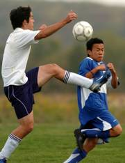 Seabury academy's aaron chung, left, heads down the field controlling the ball as K.C. Sumner's Yovanni Rojas tries to stay out of the way.