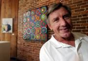 Four-time Olympic gold medalist and former Kansas University athlete Al Oerter stands in front of some of his artwork at the ACT gallery in downtown Fort Myers, Fla. Oerter created much of his art by smashing a discus into puddles of paint on canvas.