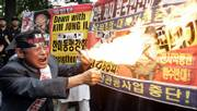 "A South Korean protester burns a banner bearing a picture of North Korean leader Kim Jong Il during an anti-North Korea rally Monday in Seoul. North Korea said Monday it performed its first nuclear weapons test. The North&squot;s official Korean Central News Agency said the test was successful, with no leak of radiation, and this was ""a stirring time when all the people of the country are making a great leap forward in the building of a great prosperous powerful socialist nation."""
