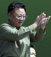 North Korean leader Kim Jong Il claps as soldiers salute him during a military parade in 2002.