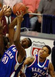 Kansas' Julian Wright, left, comes down with a rebound in front of teammate Brandon Rush in this file photo from last season's KU-Texas contest in the Big 12 Conference tournament championship game. Wright and Rush on Wednesday were named Big 12 co-players of the year.