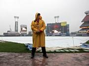 Security guard Howard Broad stands in the rain at Shea Stadium before Game 1 of the National League championship series was postponed on Wednesday in New York.