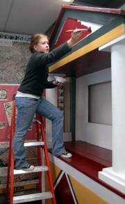 "Sydney Seratte, 17, a senior at Lawrence High School and a member of the Latin Club, paints Thursday on a replica of the ""House of Vettii,"" a home of a well-to-do resident of the ancient city of Pompeii."
