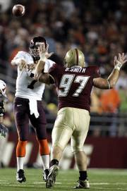 Virginia Tech quarterback Sean Glennon (7) gets off a pass under pressure from Boston College tackle Brady Smith. B.C. upset the Hokies, 22-3, Thursday in Boston.