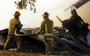 Firefighters work to extinguish a blaze at a home that exploded Thursday near Emporia. One person was confirmed dead in the afternoon explosion and subsequent fire.