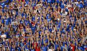 Kansas University football fans cheer during the Jayhawks' early-season victory against Louisiana-Monroe at Memorial Stadium. Sales of athletic apparel is big business in Lawrence, both from licensed and unlicensed vendors. Being able to tell the difference is at the heart of a lawsuit that pits Kansas Athletics Inc. versus Joe-College.com.