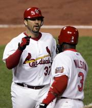 St. Louis pitcher Jeff Suppan, left, accepts congratulations from Preston Wilson after hitting a home run against New York. The Cardinals defeated the Mets, 5-0, on Saturday night in St. Louis.