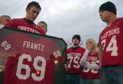 Mitchell McGinnis, left, holds a framed jersey of his best friend Lucas Frantz's Tonganoxie High School football jersey in this October 2005 file photo. Frantz's widow, Kelly Frantz, second from right, is wearing Lucas' number.