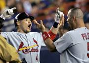 St. Louis' Yadier Molina, left, celebrates with Albert Pujols after hitting a two-run, ninth-inning homer. The blast was decisive in the Cardinals' 3-1 victory Thursday night in New York.