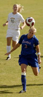 Kansas' Afton Sauer heads the ball downfield as Baylor's Anna Schuch trails.