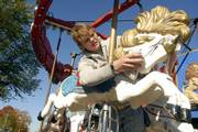 Matt Blunt, a crew member of Toby's Carnival of Arma, wipes down one of the horses on the carousel set up for the Baldwin Maple Leaf Festival today. The annual event will host a number of booths, along with a parade and carnival.