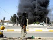 A masked gunman stands on a street corner as a building burns nearby Friday in the southern Iraqi town of Amarah, Iraq. Mahdi Army, the Shiite militia run by anti-American cleric Muqtada al-Sadr seized control of the southern Iraqi city of Amarah on Friday after their fighters stormed three main police stations, planting explosives that flattened the buildings.