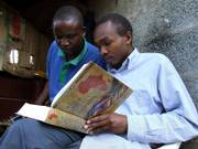 Kenyans read an example of the Africa Bible Commentary in a roadside kiosk in Nairobi. The Africa  Bible Commentary seeks to make the Bible relevant to Africans, using local proverbs and idioms to apply the book's teachings to contemporary problems such as AIDS, tribalism and female genital mutilation.