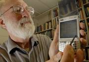 Gary Minden, professor of electrical engineering at Kansas University, demonstrates the capabilities of his new Hewlett-Packard 6945, which has many wireless options and is similar to the new 3G phones soon to hit the consumer market.