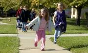 Kindergartners Lydia Wood, 5, and Katie Babbit 6, skip on their way home Monday from Deerfield School. Revised estimates from the U.S. Census Bureau show that Douglas County's population is 111,519, which is 9,000 higher than a previous challenged estimate.