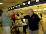 Rusty Moore, Lawrence, left, high-fives Penny Fowler, Lawrence, after Fowler picked up a spare during their bowling league action at Royal Crest Lanes, 933 Iowa. Fowler moved to Lawrence from Florida in 2003 to be near her daughter.