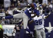 New York Giants wide receiver Plaxico Burress (17) pulls in a 50-yard touchdown pass in front of Dallas safety Patrick Watkins. The Giants won, 36-22, Monday in Irving, Texas.