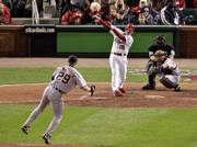 St. Louis' Jim Edmonds hits a two-run double off Detroit pitcher Nate Robertson. Looking on are Tigers catcher Ivan Rodriguez and home-plate umpire Wally Bell. The Cardinals blanked the Tigers, 5-0, on Tuesday night in St. Louis to take a 2-1 lead in the World Series.