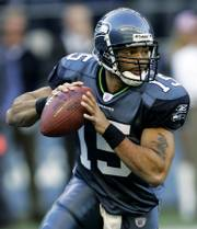 Seattle quarterback Seneca Wallace scrambles against Minnesota. Wallace, who starred at Iowa State from 2001-2002, will start Sunday at Arrowhead Stadium.