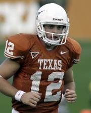 Texas quarterback Colt McCoy returns to the bench after tossing a touchdown pass against Sam Houston State on Sept. 30 in Austin, Texas.
