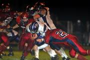 Baldwin's Sam Beecher, center, is tackled by Chad Krutz. Eudora stopped Baldwin, 14-0, Thursday in Eudora and secured its first undefeated regular season since 1948.