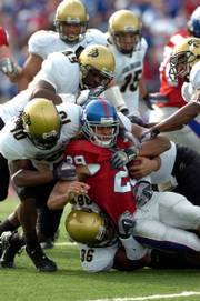 Kansas' Jon Cornish is brought to the ground by a gang of Colorado Buffaloes in the first half on Saturday at Memorial Stadium.