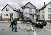 Workers examine damage after a 165-foot-tall crane toppled in high winds onto three house next to Maine Medical Center in Portland, Maine. Two people in a passing car narrowly avoided the falling crane Sunday. No one in the houses was injured.