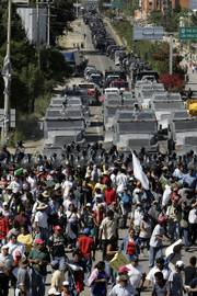 Mexican federal police push back protesters as they enter the city of Oaxaca. Federal police with assault rifles and riot shields advanced Sunday, pushing past barricades of burning tires and tree trunks in the normally picturesque tourist destination racked by five months of protests and violence.