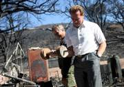 California Gov. Arnold Schwarzenegger picks up a dumbbell in the burned garage of the home of Phil Reddish, left, in Twin Pines, Calif. Schwarzenegger toured some of the ravaged area on Sunday, and attended services for one of four firefighters killed by the wildfire last week.