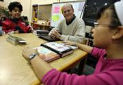 Kimberly Buzbee, 10, right, a fifth-grader at Lowman Hill Elementary School in Topeka, tells Channing Cox, center and Orlando Nunez, 10, about the books she is reading for the College Prep Academy of Topeka.