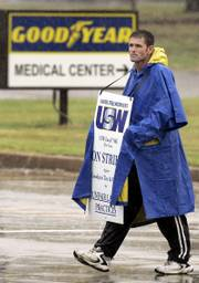Bill Brown, a Goodyear Tire & Rubber Co. employee, walks the picket line at the front gate of the factory earlier this month in Tyler, Texas. Goodyear said Monday that it plans to close the Tyler plant three weeks after workers at the plant and 15 others went on strike.