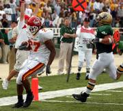 Iowa State'S Stevie Hicks, left, runs past Baylor's Justin Crooks in a 2004 game. Hicks, the Cyclones' starting running back, is scheduled to have his knee 'scoped today and will not play Saturday against Kansas University.