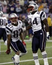 New England receiver Reche Caldwell (87) celebrates with tight end Benjamin Watson (84) after Caldwell's first-quarter touchdown. Watson later scored on another pass from Tom Brady on Monday in Minneapolis.