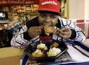 Edward Patterson, a KFC employee, eats some of the company's trans fat-free products in New York. KFC said Monday it is phasing out trans fats in cooking its original recipe and extra-crispy fried chicken, potato wedges and other menu items, but hasn't found a good alternative yet for its biscuits.