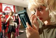 """Kansas University sophomore Valerie Metzler, of Bonner Springs, adds some makeup as other students pose for photographs during a costume contest before a movie at the Kansas Union Ballroom. Students were dressing up as their favorite characters from the cult classic movie """"The Rocky Horror Picture Show,"""" which was shown Monday night at the Ballroom."""