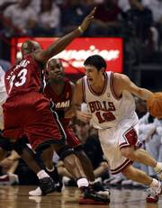 Chicago guard Kirk Hinrich (12) drives past Miami Heat center Alonzo Mourning (33) and guard Gary Payton. The former Kansas University standout scored 26 points - and a five-year, $47.5 million contract extension - Tuesday. The Bulls pummeled the defending champions, 108-66.