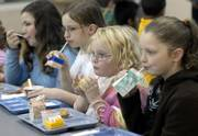 Alexcis Estelle, second from right, and Hannah Abell, right, both second-graders at New York School, join their classmates and eat a morning breakfast. Nutrition experts say people who eat breakfast have a better daily nutrient intake than those who don't and are less likely to be overweight.