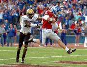 Kansas freshman quarterback Todd Reesing jumps into the end zone as Colorado's Lionel Harris in futile pursuit. Reesing made an impressive collegiate debut Saturday in a 20-15 victory over the Buffaloes.