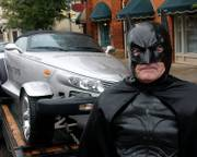 "George Perkins, known as Batman, stands near his ""Batmobile"" on Oct. 27 in downtown Americus, Ga. Perkins, a resident of Union Springs, Ala., has helped about 40 Americus residents rid their homes and offices of bats, but the town&squot;s historic district still has a serious bat problem. He normally wears ordinary clothes, but puts on the Batman outfit for parades."