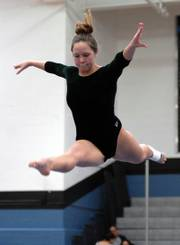 "Free State High&squot;s Laura Devlin performs on the balance beam. Devlin qualified individually for Saturday&squot;s state meet and took fifth on the bars in Prairie Village despite a sprained ankle. ""Bars are where it&squot;s at,"" she said."