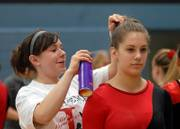 University of Kansas Freshman Lindsey Fisher hair sprays Kara Kellison's hair in place before Kellison preforms on the uneven parallel bars. Kellison competed in the girls Gymnastics State Championship at Shawnee Mission East Saturday afternoon.