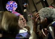 Presiding Bishop of The Episcopal Church Katharine Jefferts Schori, center, blesses a woman following a ceremony in which Jefferts Schori was installed as presiding bishop during a ceremony Saturday at the National Cathedral in Washington, D.C.