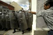 A protester confronts Mexican federal police officers Saturday in Oaxaca, Mexico. Demonstrators plan to march Sunday from the Oaxaca University to police encampments in the center of the city as part of their five-month protest to oust the state's governor.