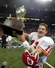 Kansas City's Damon Huard hoists the Missouri Governor's Cup. Huard threw three touchdowns Sunday in St. Louis.